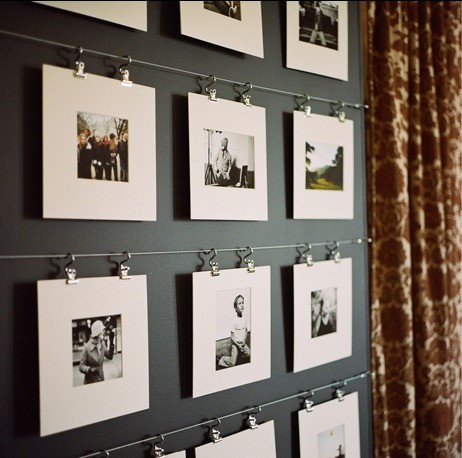 Images hanging from wire and clips on a dark wall