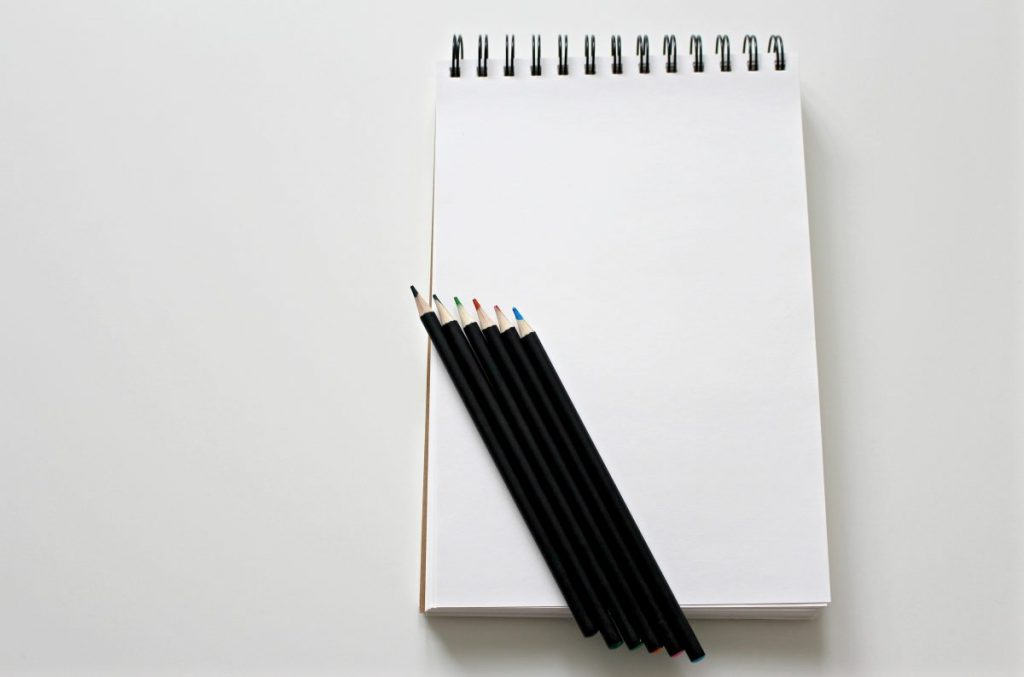 Pencils on a blank notebook.