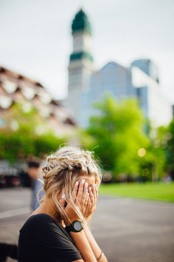 A blonde woman hiding her face