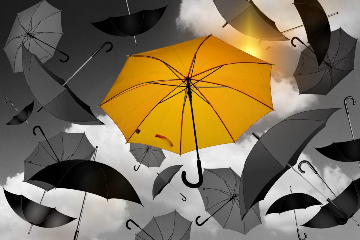 One yellow umbrella in a bunch of black umbrellas